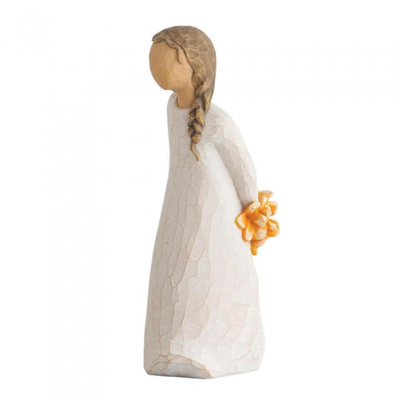 resin figurine of a lady standing with yellow flowers