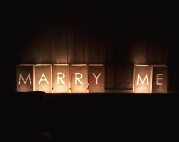A candle with 'Will You Marry Me?'